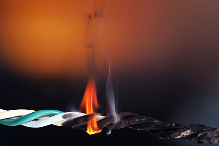 An electrical wire on fire due to overloading or short circuit