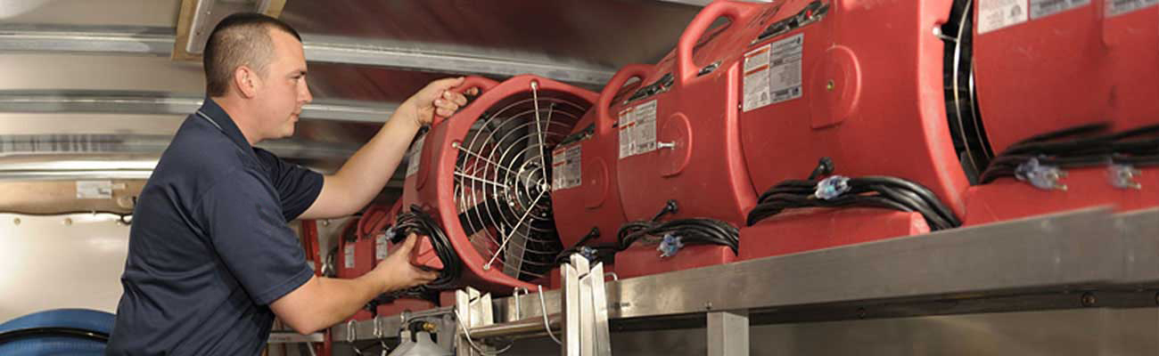 a restoration technician arranging fans inside a truck